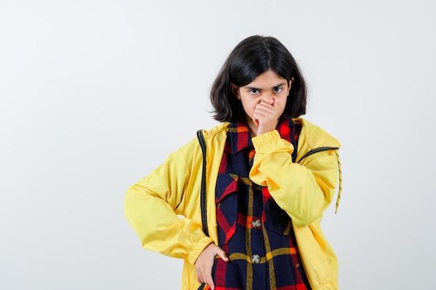 Portrait de petite fille pinçant le nez dans une chemise à carreaux, une veste et une jolie vue de face