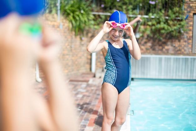 Portrait de petite fille portant des lunettes de natation au bord de la piscine