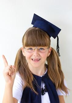 Portrait petite fille porte un chapeau diplômé et sourit avec bonheur pour le concept de l'éducation