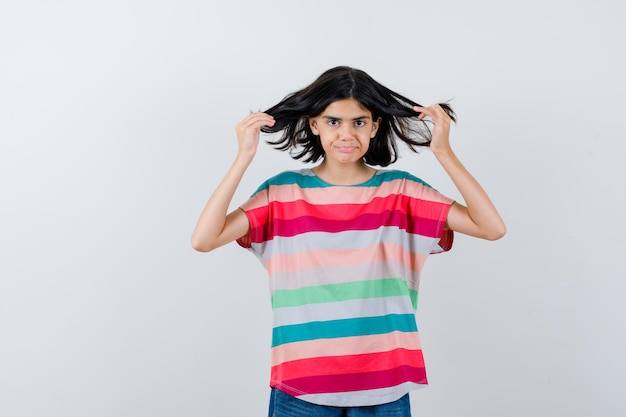 Portrait de petite fille posant avec des cheveux volants en t-shirt et à la belle vue de face