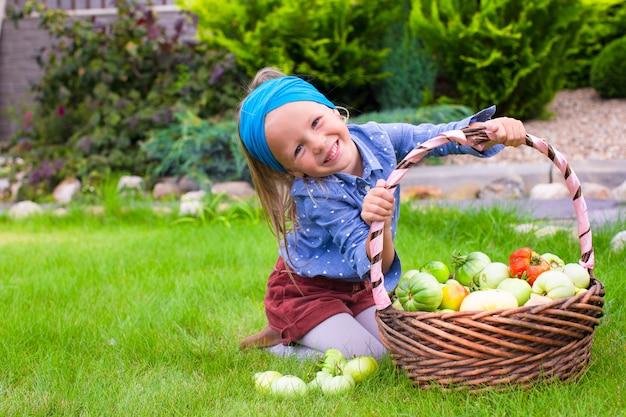 Portrait de petite fille avec récolte d'automne de tomates dans des paniers