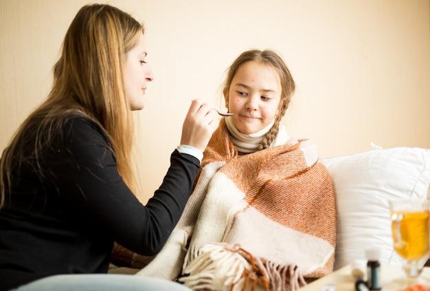 Portrait de petite fille refusant de boire des médicaments donnés par la mère