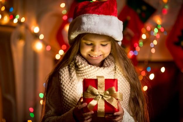 Portrait de petite fille regardant la boîte ouverte avec le cadeau de noël