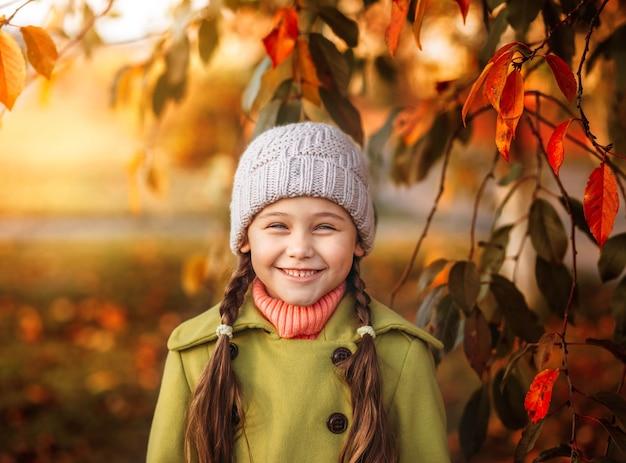 Portrait d'une petite fille en riant dans un parc d'automne