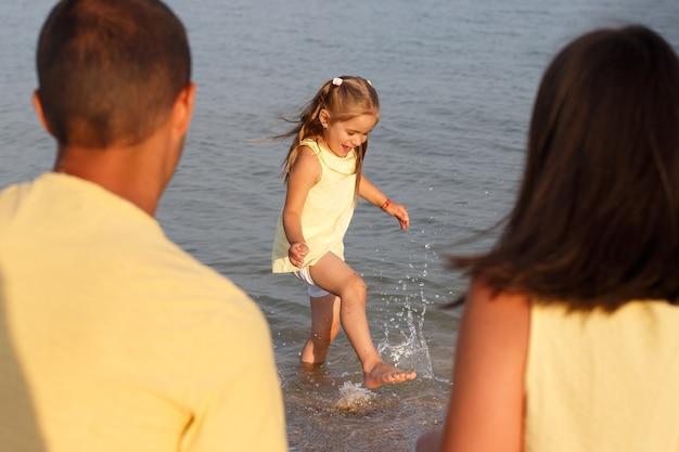 Portrait d'une petite fille riante en vêtements jaunes courant au bord de la mer