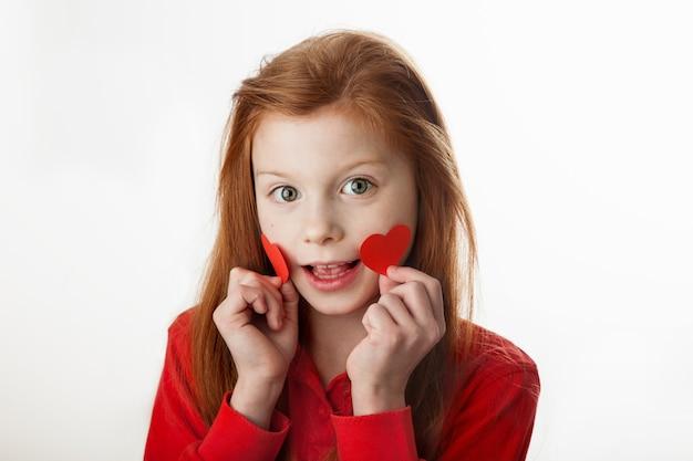 Portrait de petite fille rousse souriante couvrant ses joues avec des coeurs rouges.
