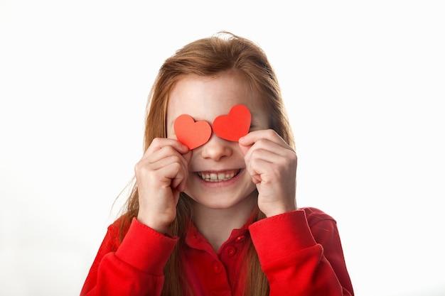 Portrait de petite fille rousse souriante couvrant ses yeux avec des coeurs rouges.