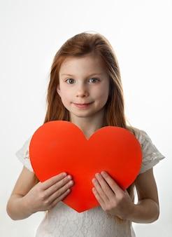 Portrait de petite fille rousse souriante tenant grand coeur rouge dans ses mains sur fond blanc.