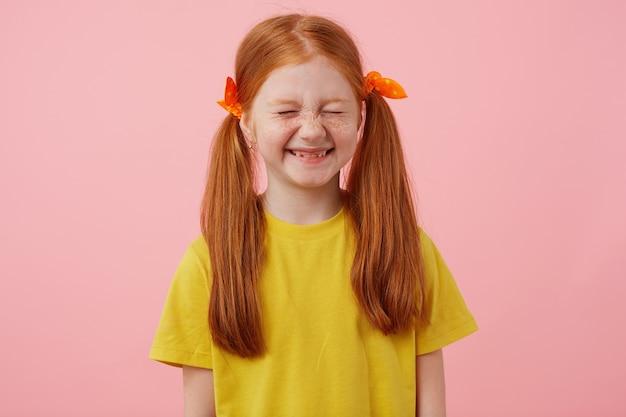 Portrait de petite fille rousse de taches de rousseur avec deux queues, sourit les yeux fermés, porte en t-shirt jaune, se dresse sur fond rose.