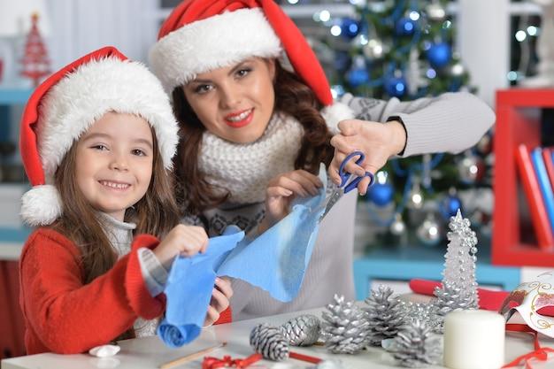 Portrait de petite fille avec sa mère se préparant à noël