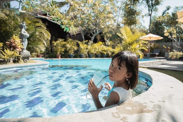 Portrait d'une petite fille se détendre dans la piscine tout en dégustant une boisson fraîche seule