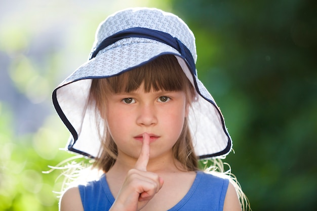 Portrait de petite fille sérieuse au grand chapeau