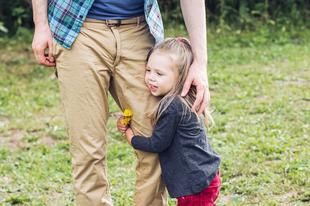 Portrait d'une petite fille serrant son père sur une pelouse d'été par une chaude journée d'été. fête des pères