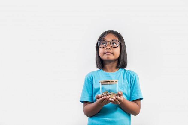Portrait de petite fille avec ses économies en studio photo
