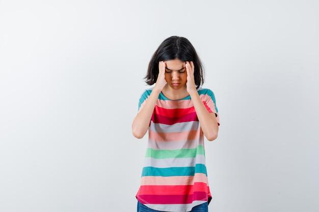 Portrait de petite fille souffrant de forts maux de tête en t-shirt et à la vue de face fatiguée
