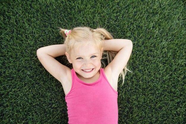 Portrait d'une petite fille souriante allongée sur l'herbe verte