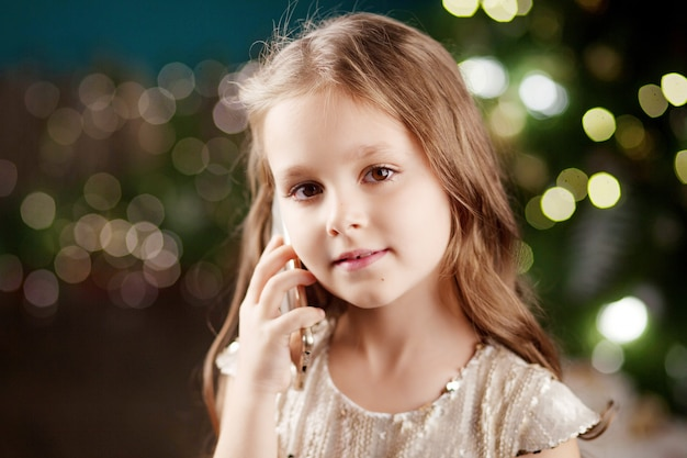 Portrait d'une petite fille souriante aux cheveux longs en robe sur les lumières de noël. petite fille parle au téléphone nouvel an et noël.