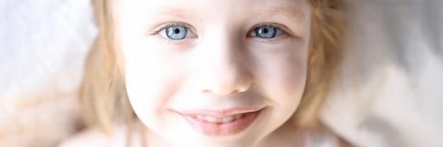 Portrait de petite fille souriante aux yeux bleus