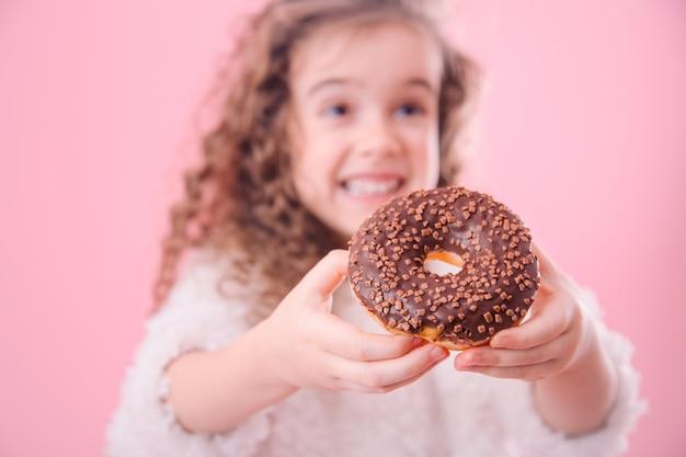 Portrait d'une petite fille souriante avec des beignets