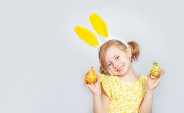 Portrait d'une petite fille souriante caucasienne mignonne avec des oreilles de lapin et des décorations pour pâques dans les mains.