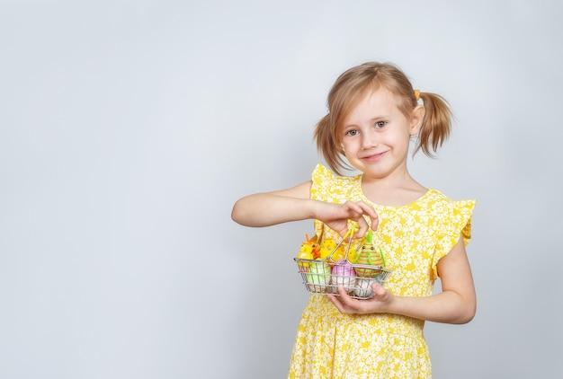 Portrait d'une petite fille souriante caucasienne mignonne avec un panier rempli de décorations de pâques.