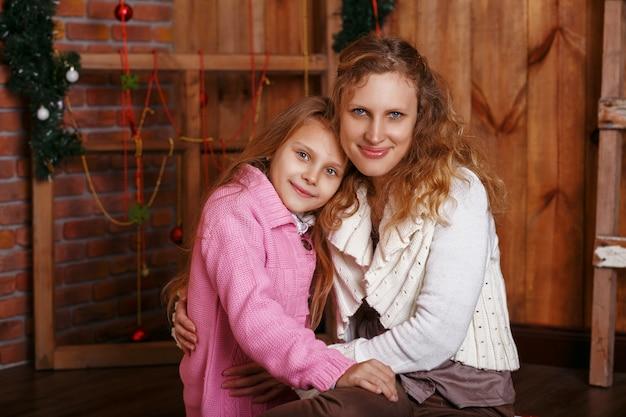 Portrait de petite fille souriante heureuse avec sa mère assise parmi les décorations de noël