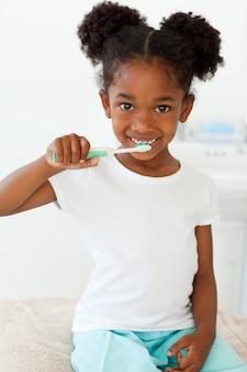 Portrait d'une petite fille souriante se brosser les dents