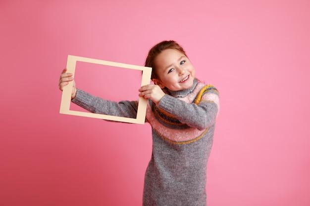 Portrait d'une petite fille souriante tenant un cadre vierge pour une maquette sur fond rose.