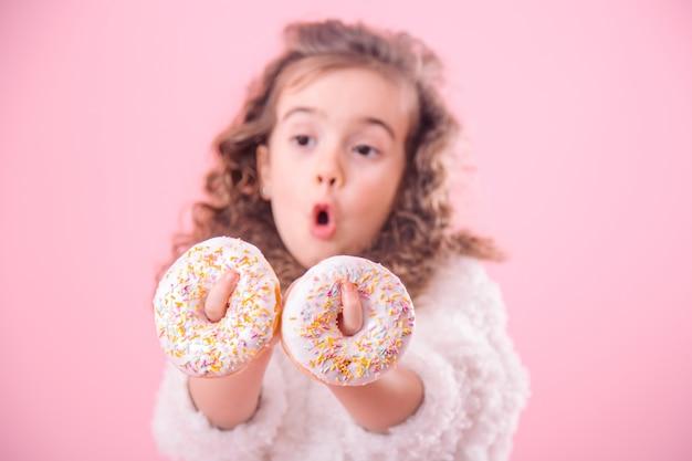 Portrait d'une petite fille surprise avec des beignets
