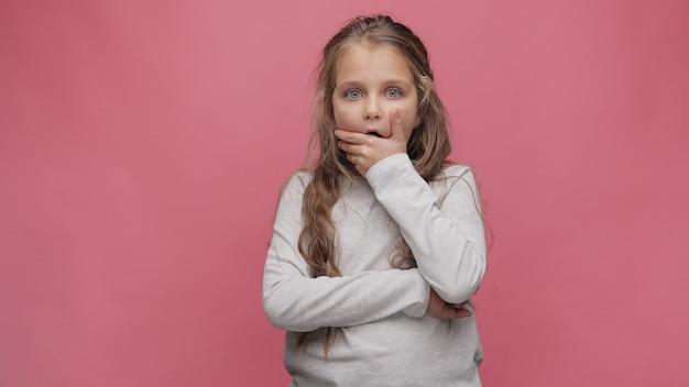 Portrait de petite fille surprise à fond rose. jolie fille aux cheveux bouclés ouvrant les yeux et regardant la caméra.