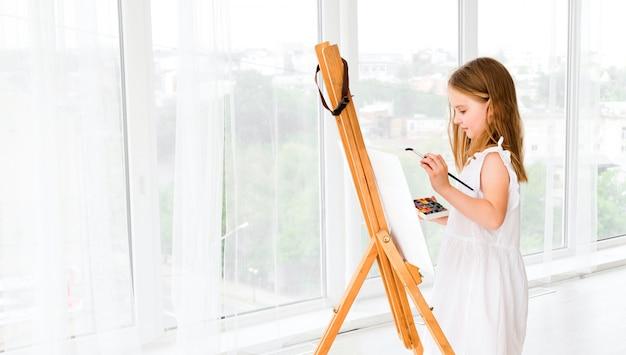 Portrait de petite fille surprise peignant une image
