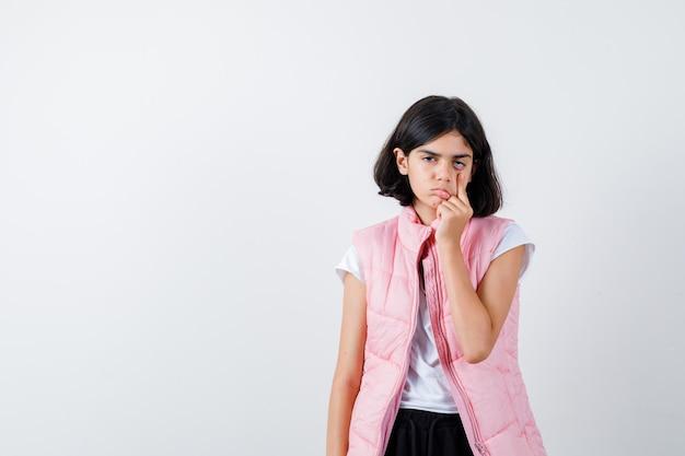 Portrait d'une petite fille en t-shirt blanc et gilet matelassé