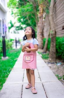 Portrait de petite fille en tablier avec du mortier dans le jardin