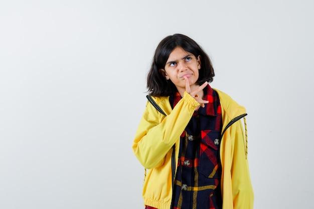 Portrait de petite fille tenant le doigt sur la bouche en chemise à carreaux, veste et à la vue de face réfléchie