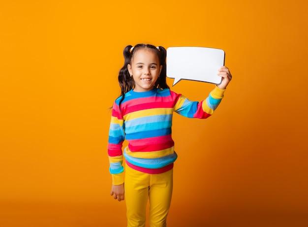 Portrait d'une petite fille tenant un nuage de papier vide méditant sur une idée.