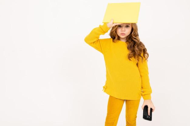 Portrait de petite fille tenant un papier vierge et smartphone