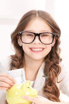 Portrait de petite fille avec tirelire et argent