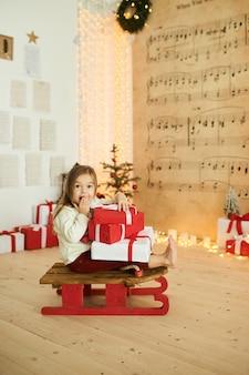 Portrait d'une petite fille sur un traîneau rouge avec un cadeau sur un fond de lumières floues