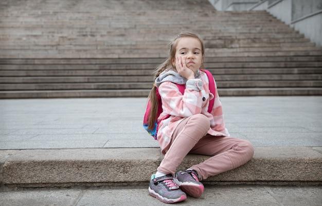 Portrait d'une petite fille triste avec une mallette sur le dos, assise sur les escaliers. retour à l'école.