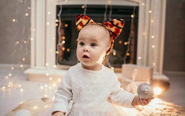 Portrait d'une petite fille vêtue d'une robe moelleuse et d'un bandeau avec des oreilles de tigre assis près de la cheminée dans la chambre et jouant avec des boules de noël