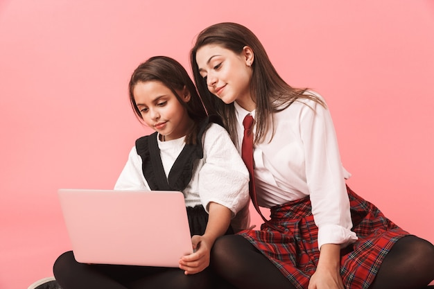 Portrait de petites filles en uniforme scolaire à l'aide d'un ordinateur portable, assis sur le sol isolé sur mur rouge