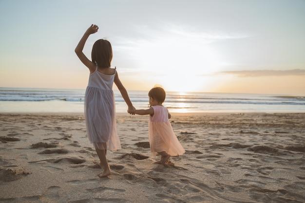 Portrait de petites sœurs profitant de vacances sur la plage
