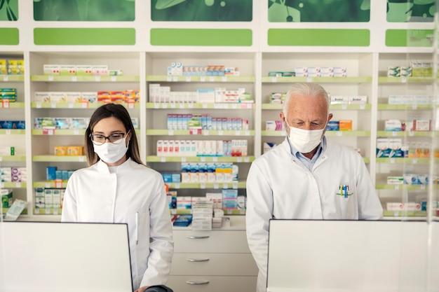 Portrait d'un pharmacien et virus corona. un pharmacien âgé et une apothicaire adulte se tiennent derrière le comptoir d'une pharmacie et vendent des médicaments. ils portent des uniformes et des masques faciaux