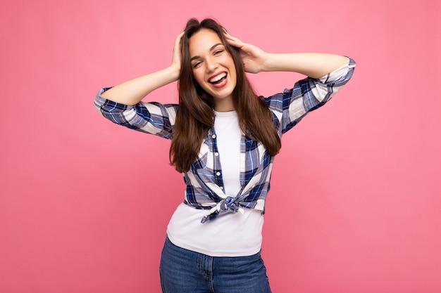 Portrait photo de la belle jeune femme brune hipster souriante en chemise bleue et blanche à la mode et