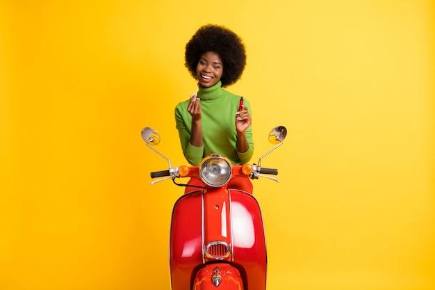 Portrait photo d'une conductrice de vélo femme brune à la peau noire décontractée appliquant un brillant à lèvres rouge avec un pinceau isolé sur un fond de couleur jaune vif