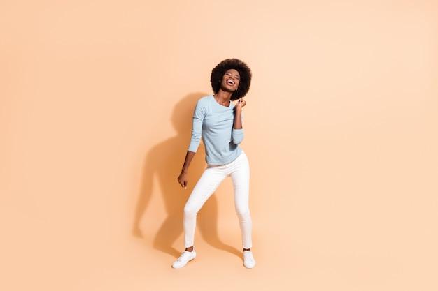 Portrait photo corps entier d'une fille afro-américaine énergique dansant isolée sur fond de couleur beige pastel