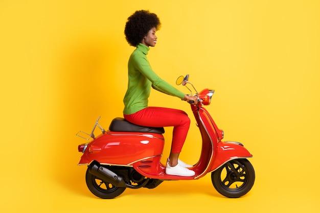 Portrait photo d'une femme afro-américaine brune chevauchant une moto rouge isolée sur fond de couleur jaune vif