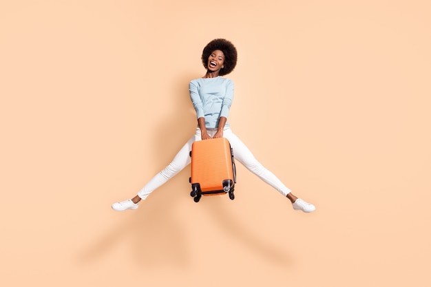 Portrait photo d'une femme afro-américaine ravie tenant une valise orange sautant avec les jambes écartées, bouche ouverte isolée sur fond de couleur beige pastel
