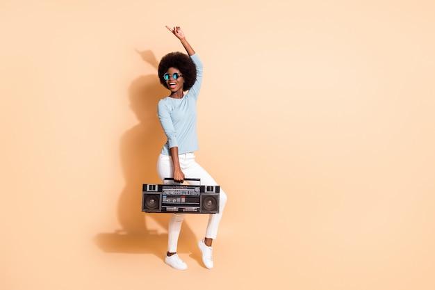 Portrait photo d'une femme afro-américaine tenant une boombox pointant un doigt vers le haut dansant isolé sur fond de couleur beige pastel