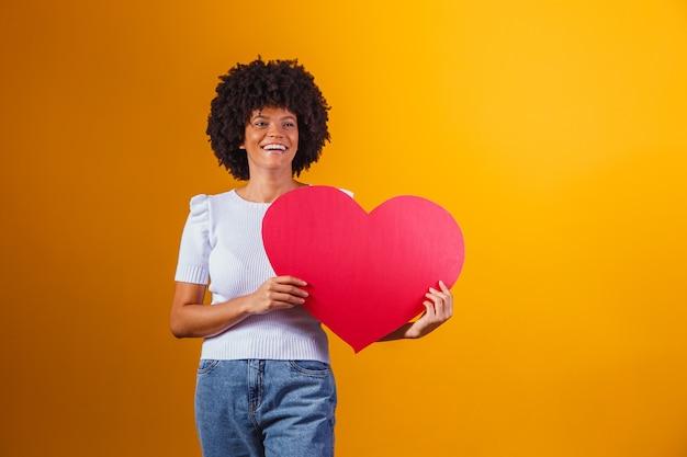 Portrait photo d'une femme afro souriante tenant une grande carte de coeur rouge